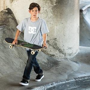 Garçon portant des vêtements de la marque Dc Shoes avec un skateà la main
